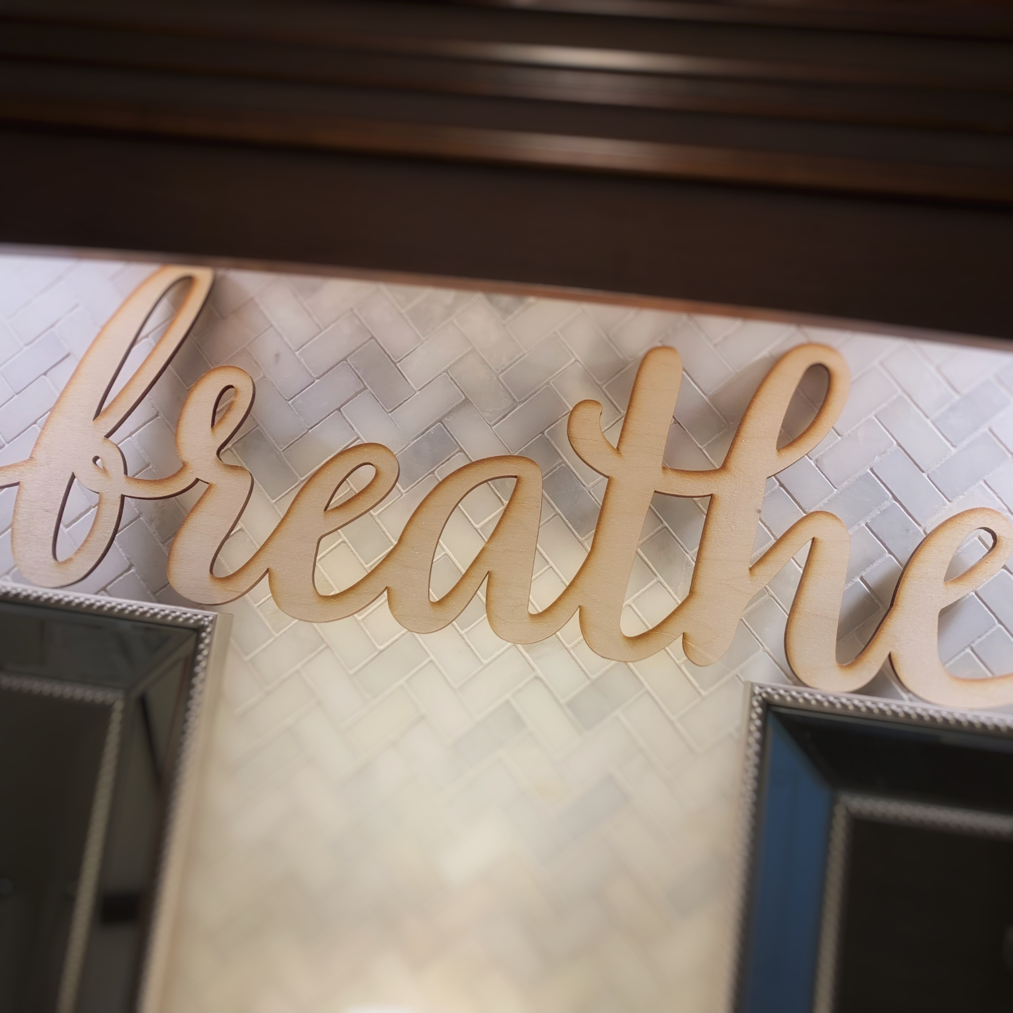 """Wood cut sign that says """"breathe"""" in script"""