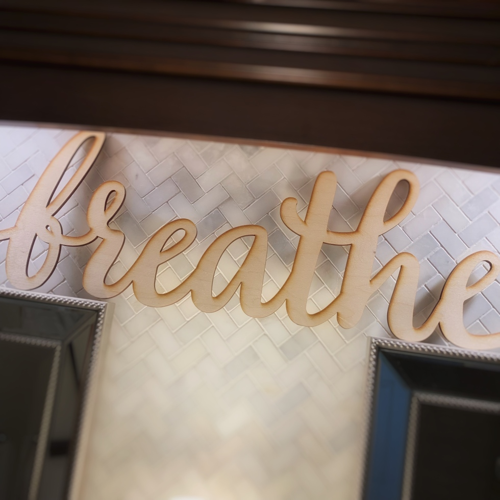 "Wood cut sign that says ""breathe"" in script"